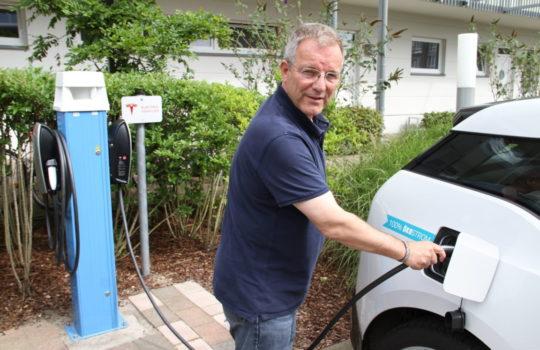 Strom-Zapfsäule für Gäste direkt am Boardinghouse: Hotelmanager Rüdiger Magowsky mit dem Firmenwagen.
