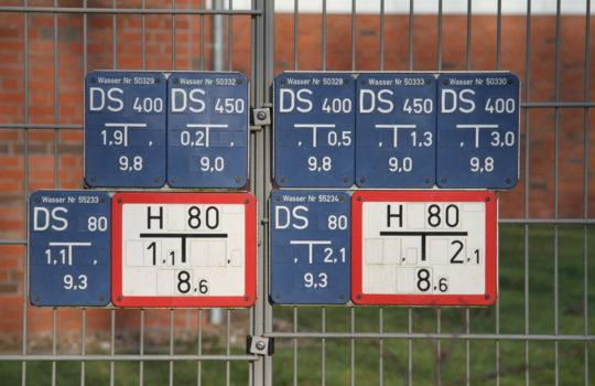 Zeigen deutlich, dass hier Wasser gefördert wird: die Hinweise auf die Entnahmestellen am Zaun des Wasserwerkes Bexhövede. Foto: Helmut Stapel